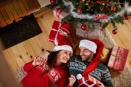 embraced: Couple in love lying under the Christmas tree in wooden house