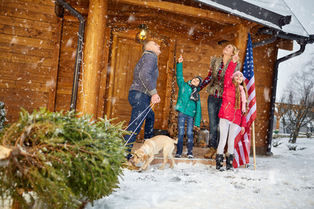 pappy: Happy family with Christmas tree on snowy day enjoying