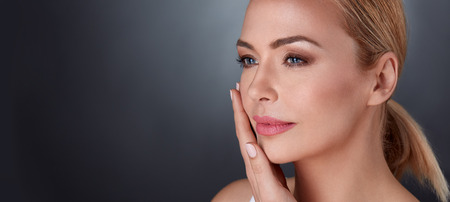 softness: beautiful middle aged female touching her face skin and feel the softness
