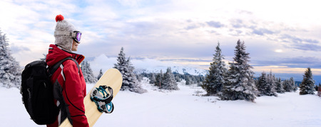 Woman with snowboard on snowy mountain, idyllic day for sport