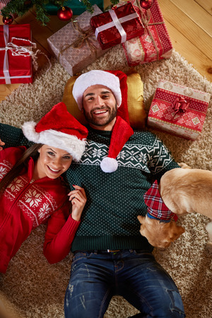 woman laying: Young couple enjoy under the Christmas tree