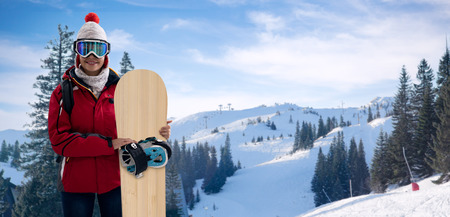 Smiling woman in snowy mountains, extreme sport and winter holiday. Young beautiful woman with ski mask holding her snowboard at ski slope