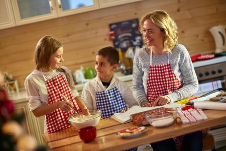 les enfants et la mère préparant Noël biscuits-famille le temps Banque d'images