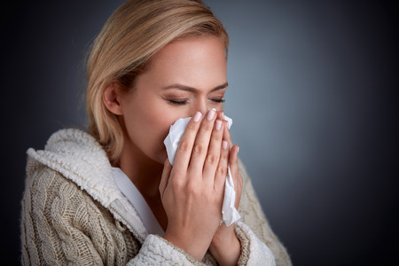 nighty: woman having flu, feeling bad and blowing her nose