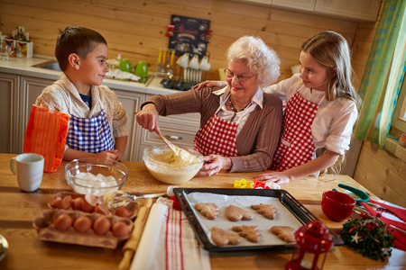 grandmother enjoying with grandchildren preparing Christmas cookies at home