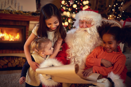 wish  list:  Real Christmas father reading wish list with mixed race little girls