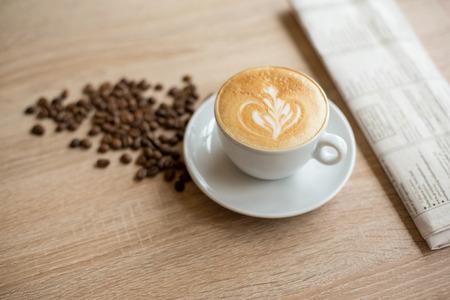 Tazza di caffè e caffè di fagioli sul tavolo di legno