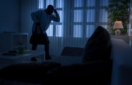cambriolage ou voleur effraction dans une maison la nuit par une porte arrière, vue de l'intérieur de la résidence.