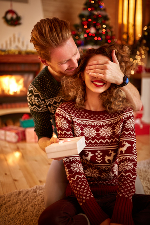 shinning: Young man surprising woman with present for New Year Stock Photo