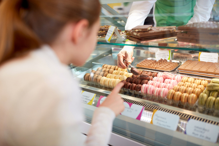 chocolate biscuit: Girl choose chocolate macarons in confectionary store from showcase