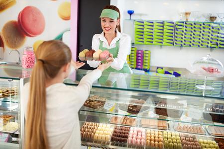Glimlachende vrouwelijke banketbakker verkopen heerlijke macarons aan meisje in patisserie