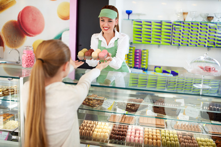 Smiling female confectioner sales delicious macarons to girl in pastry shop