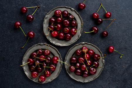 close up view: fresh cherry in vintage silver plate over dark grunge background, top  view, close up Stock Photo