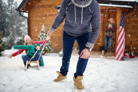 fun sledding- Family enjoying on winter holiday Stock Photo