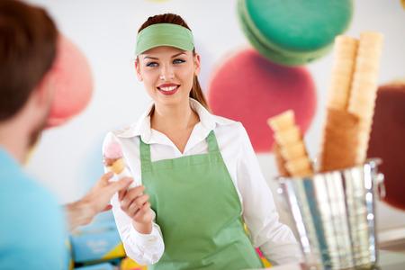 アイスクリームを顧客に与える菓子の美しい女性労働者 写真素材