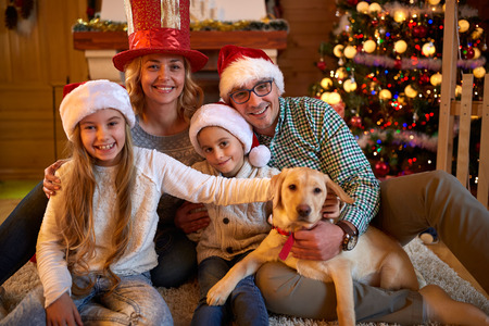 christmas time: Portrait of a happy family and the dog spending together Christmas time at home
