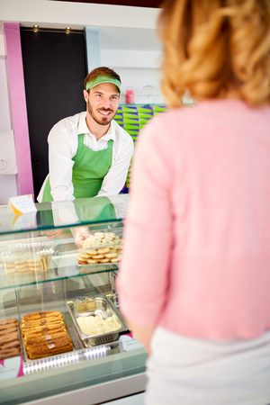 Young vendor in pastry shop attending woman Stock Photo