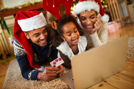 realize:  afro African family realize Christmas shopping online from warm living room at home