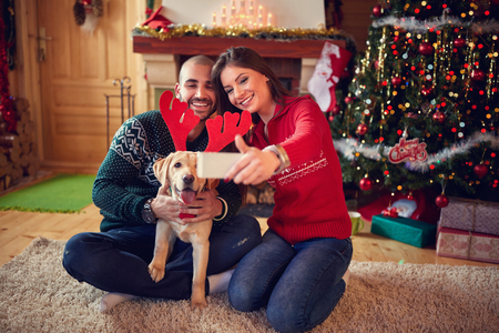 young tree: Couple making selfie with dog with reindeer horn for Christmas Stock Photo