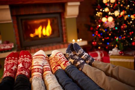 Feet in wool socks near fireplace in winter, family at home near fire
