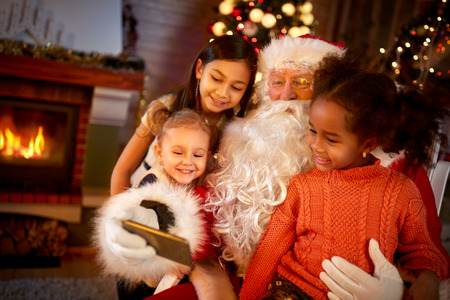 carefully:  Santa Claus sharing smart phone with children in Christmas atmosphere