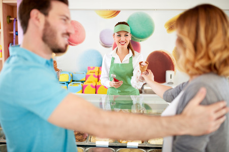 bakery store: Smiling saleswoman gives ice cream to woman in bakery store