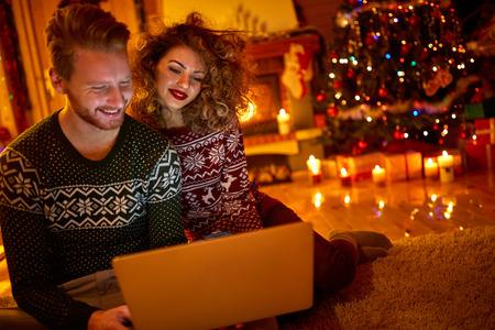 Jeune couple cherche sur un ordinateur portable à la veille de Noël Banque d'images - 66845030