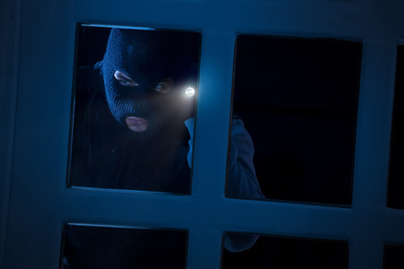 Burglar with flashlight looking through the window Banco de Imagens