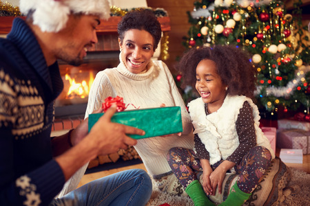 fireplace family: Smiling lovely girl receiving Christmas present from parents, happy family near fireplace