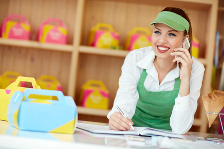 seller: Beautiful female seller in confectionery taking order with phone