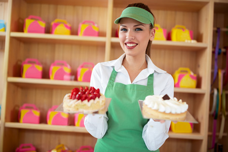 Female attractive vendor in pastry shop hold two nice cakes in hands