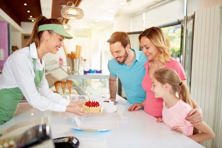 家族のためイチゴとフルーツ ケーキの包装のベーカリー店員