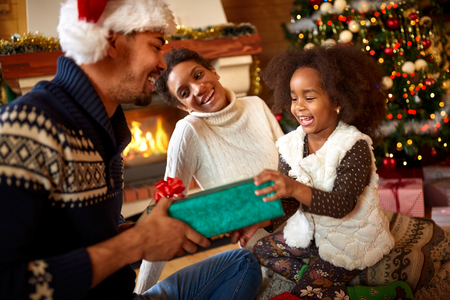 Laughing afro American family in warm Christmas atmosphere exchanging gifts for Christmas