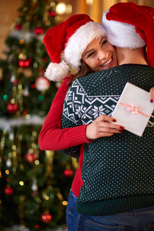 Happy girl hugging guy for Christmas gift