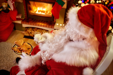 Santa Claus relaxing at home sitting in comfortable rocking chair near Christmas tree drinking milk and eating fresh cookies Stock Photo