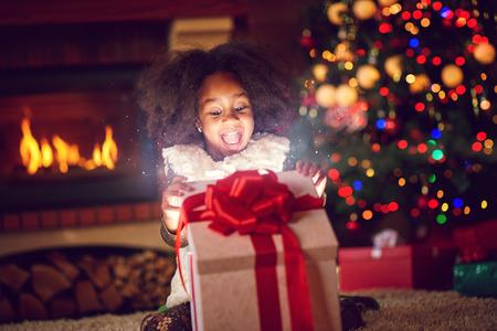 ragazza sorpresa che apre i regali di Natale magici Archivio Fotografico
