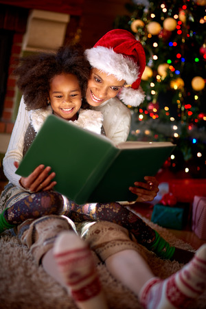 Mother is reading a book to her little girl on Christmas eve- family time Stock Photo
