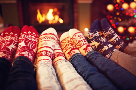 fireplace family: Family in socks near fireplace in winter on Christmas time Stock Photo