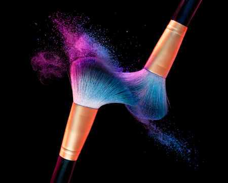 Makeup brush with blue powder explosion on black background