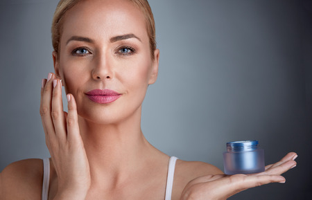 putting up: Beautiful nourished woman holding cream for her skin