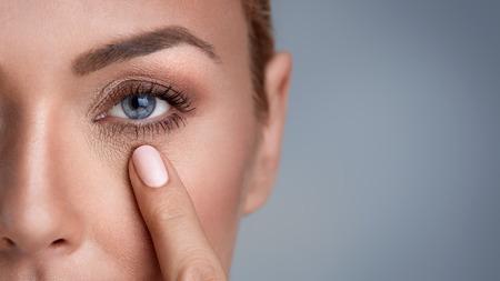 mujer que controla arrugas alrededor de los ojos, de cerca Foto de archivo