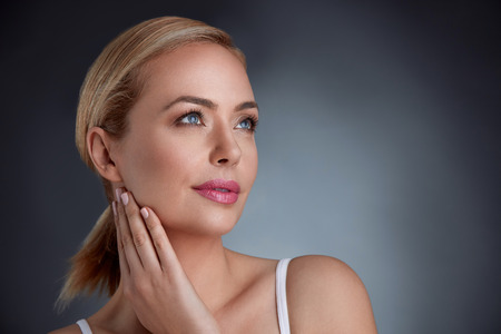 Serene woman touching her soft skin on the neck