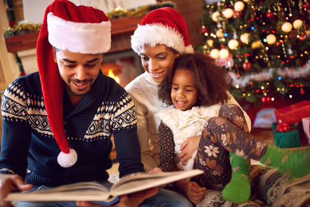 fireplace family: Happy afro American family read a book at fireplace on Christmas eve. Family with child celebrating Xmas Stock Photo