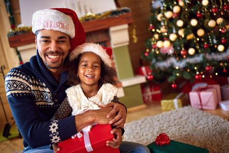 Afro American father with cute cheerful daughter for Christmas eve