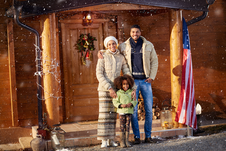 holiday house: Portrait of Afro American family front wooden house on Christmas holiday