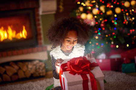 Surprised little girl looking in magic gift the magic of Christmas