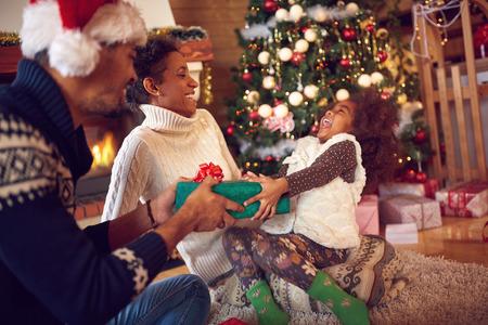 집에서 바닥에 앉아 선물을 열고 크리스마스에 행복 한 가족 스톡 콘텐츠