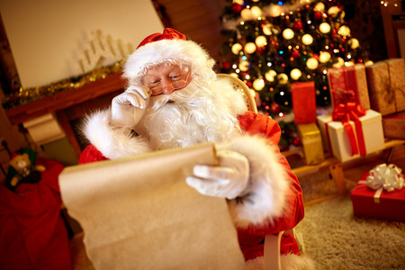 Santa Claus looking at long list with children desire for Christmas gift