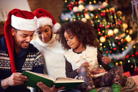 black girl: Family spending Christmas time together, daddy reading fairytales Lizenzfreie Bilder