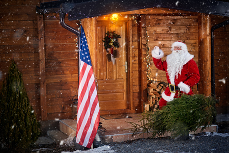 Santa Claus standing outdoor under snow and holding Christmas tree